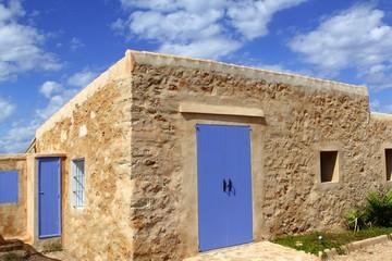 stone house masonry blue sky door windows