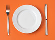 Knife, white plate and fork on orange background - 24439090