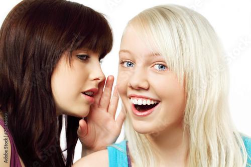 Mädchen flüstert Freundin ins Ohr