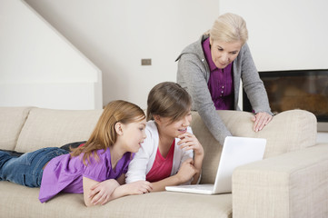 two girls using a laptop on a couch with their grandmother