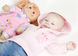 lying down baby girl with a doll