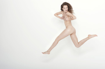 naked woman covering her breasts and jumping