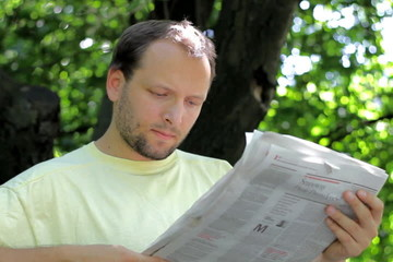 Man reading newspaper in the park