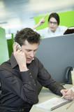 businessmen talking on a mobile phone while his colleague looking angry