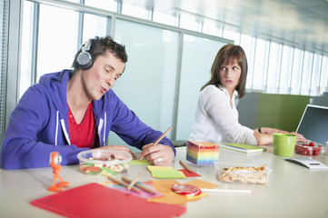 businesswoman looking at a businessman listening to headphones and writing