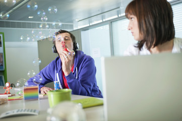 businesswoman looking at a businessman listening to headphones and blowing bubbles