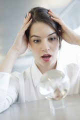 businesswoman looking at a crystal ball and looking shocked