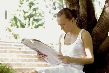 Young woman in the park reading newspaper, dolly shot