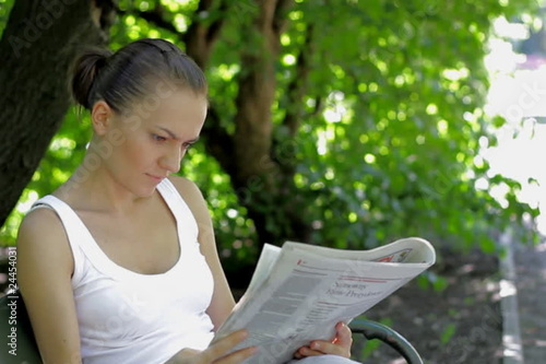 Young woman sitting in the park and reading newspaper