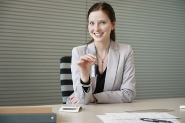 female financial advisor holding a car key in an office
