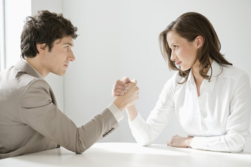 businessman arm wrestling with a businesswoman