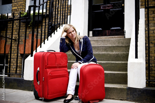 A young woman waiting on her doorstep with her suitcases