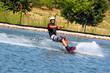 Wassersportler Mann Wakeboard wird durch das Wasser gezogen