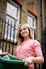 A young woman holding a recycling box, on her doorstep