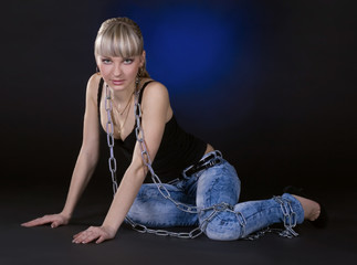 Sexy blonde in chains over black background
