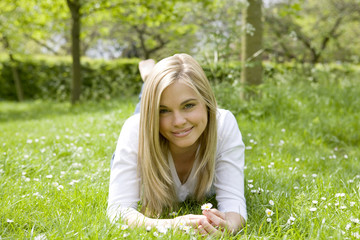 A young woman lying on the grass, smiling