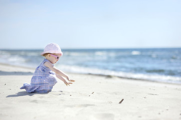 Adorable toddler girl on a sand beach