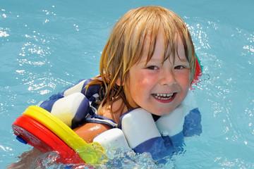 Kind mit Schwimmhilfen im Pool