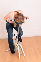 Phew.. Young woman resting on an old exercise bike