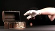 Thief stealing gold from jewel box, over black background