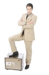 Geschäftsmann vor einem Tresor mit ernster Miene