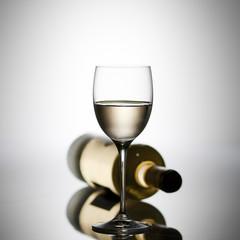 Bicchiere di vino bianco con bottiglia