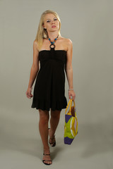young blonde fashionable girl standing with a hand bag