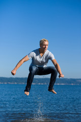 Young man jumping out of water