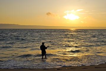 Angler beim Sonnenuntergang am Meer