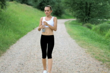 Woman drinking water after sport activities, slow motion