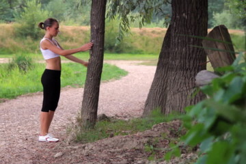Woman doing stretching exercise for her legs outdoors