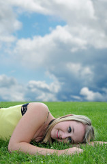 Beautiful blond young girl laying in grass