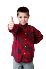 Young boy in plaid shirt giving thumbs up, studio shot
