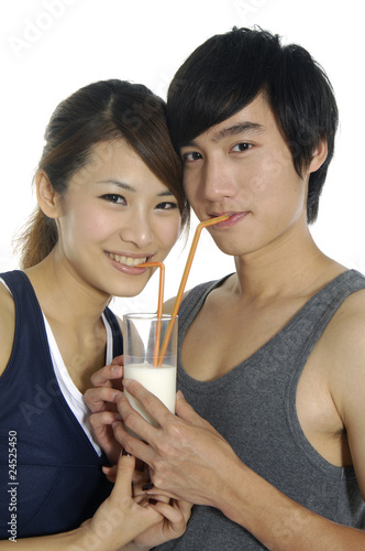 Young happy couple drinking together milk shake