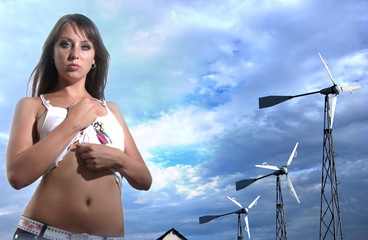 Girl with windgenerators against clouded sky