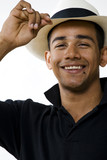 Smiling young man tipping hat