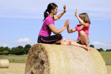 happy white family playing on hay bales