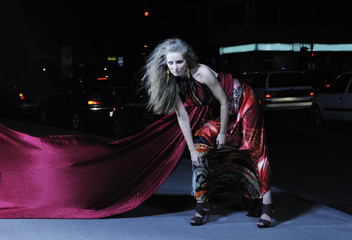 elegant woman on city street at night