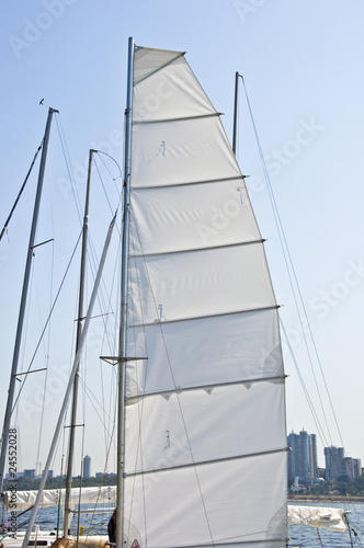 Mast yacht with a sail. Against the backdrop of the river