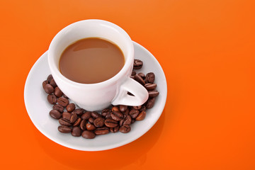 Small white cup of coffee with coffee grain on orange background