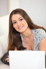 Jeune femme décontractée devant ordinateur portable