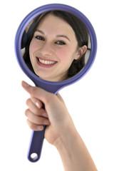 Junge freundliche Frau betrachtet sich im Spiegel