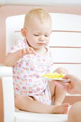 sitting toddler eating an apple