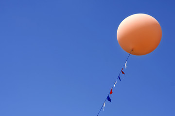 One orange balloon floating in bright blue sky
