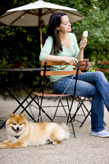 A young woman with her dog at a cafe, eating an ice cream