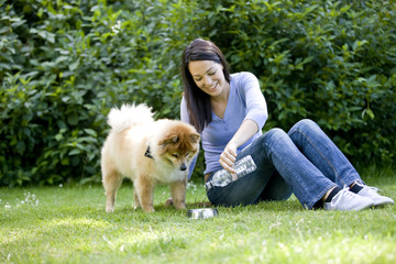 A woman sitting on the grass, pouring her dog a drink of water