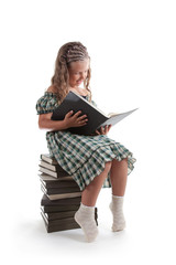 Smiling little girl with pigtails reading a book