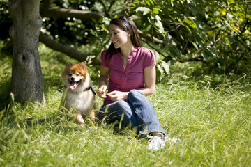 A young woman sitting on the grass with her dog in summertime