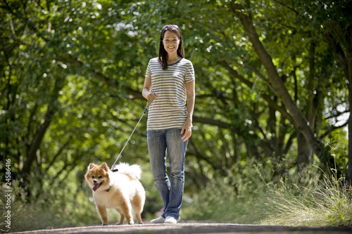 A young woman standing with her dog in summertime