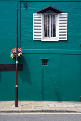 Turquoise house with hanging basket